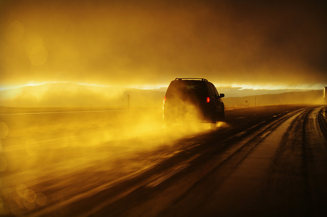 Car driving on wet road at sunset